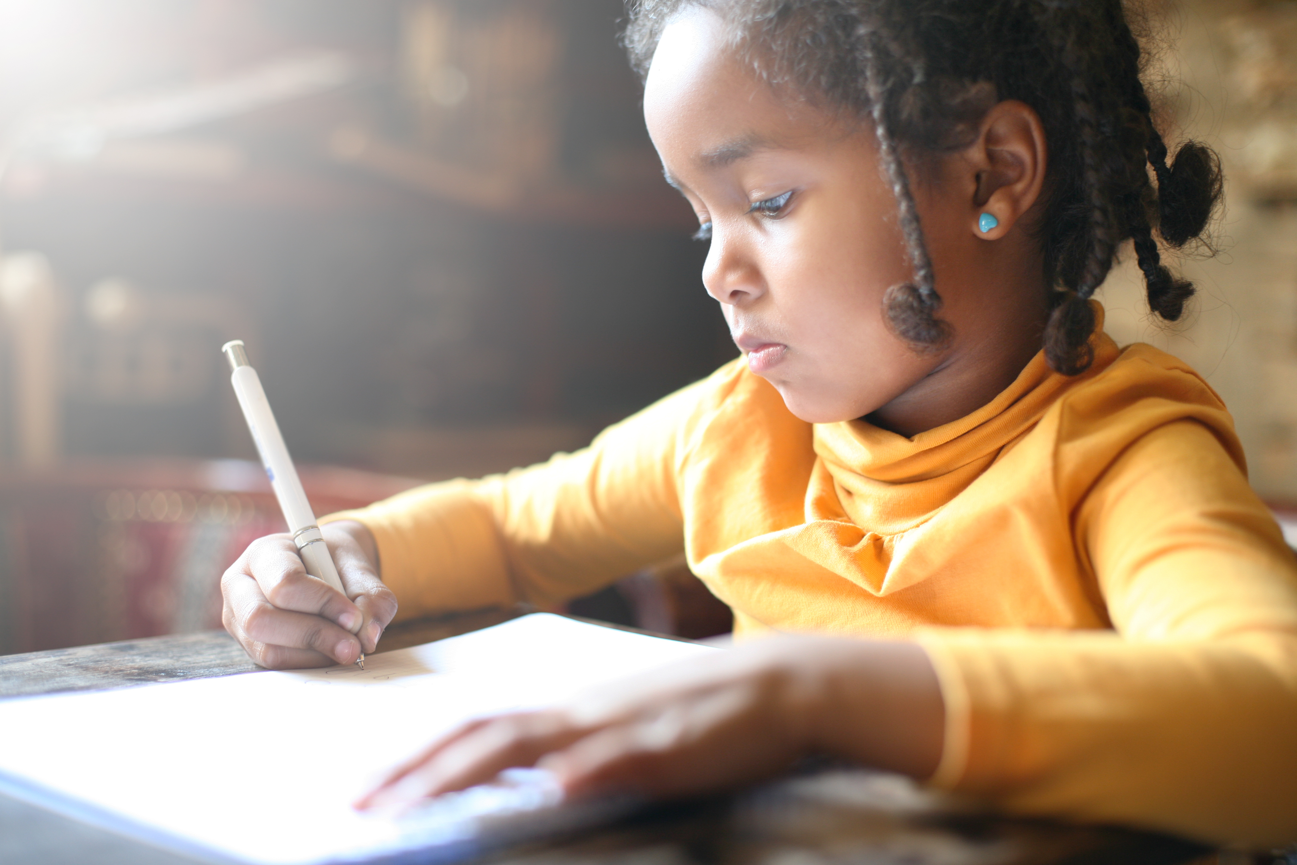 School child. African girl writing in notebook.